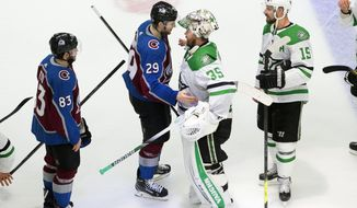 Colorado Avalanche's Nathan MacKinnon (29) and Dallas Stars goalie Anton Khudobin (35) meet after Dallas won during overtime NHL Western Conference Stanley Cup playoff game action in Edmonton, Alberta, Friday, Sept. 4, 2020. (Jason Franson/The Canadian Press via AP)