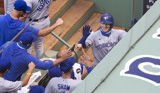 Toronto Blue Jays' Danny Jansen is congratulated by teammates in the dugout after his two-run home run against the Boston Red Sox during the second inning of the first game of a baseball doubleheader Friday, Sept. 4, 2020, at Fenway Park in Boston. (AP Photo/Winslow Townson)