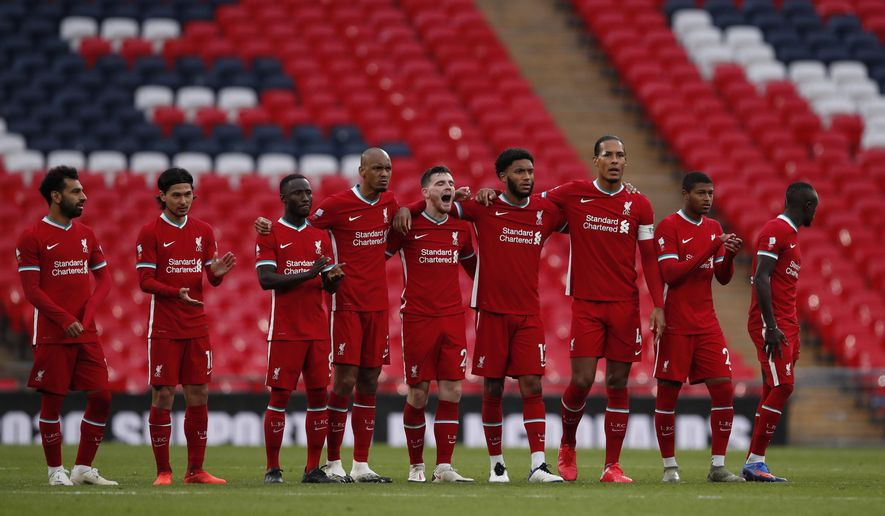 Liverpool players stand on the pitch during the penalty shootout during the English FA Community Shield soccer match between Arsenal and Liverpool at Wembley stadium in London, Saturday, Aug. 29, 2020. (Andrew Couldridge/Pool via AP)