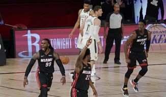 Miami Heat's Jae Crowder (99), Jimmy Butler (22) and Bam Adebayo (13) celebrate as they run up the court in front of Milwaukee Bucks' Brook Lopez (11) and Giannis Antetokounmpo (34) after a basket in the second half of an NBA conference semifinal playoff basketball game Friday, Sept. 4, 2020, in Lake Buena Vista, Fla. (AP Photo/Mark J. Terrill)