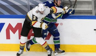 Vancouver Canucks' Brock Boeser (6) is checked by Vegas Golden Knights' Brayden McNabb (3) during first-period NHL Western Conference Stanley Cup playoff action in Edmonton, Alberta, Thursday, Sept. 3, 2020. (Jason Franson/The Canadian Press via AP)
