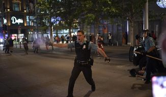 "FILE - In this Aug. 26, 2020, file photo, police spray a substance to clear the area where a colleague was down on the Nicollet Mall in Minneapolis. Two men from Minnesota and North Carolina who prosecutors say are members of an anti-government extremist group have been charged with terrorism counts for allegedly building weapons they believed were going to Hamas. They are allegedly members of the ""Boogaloo Bois."" The investigation into the men began after they posted messages on social media about inciting violence after the May 25 death of George Floyd. (Jeff Wheeler/Star Tribune via AP, File)"
