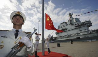 In this Dec. 17, 2019, file photo and released by Xinhua News Agency, Chinese honor guard raise the Chinese flag during the commissioning ceremony of China's Shandong aircraft carrier at a naval port in Sanya, south China's Hainan Province. Seventy-five years after Japan's surrender in World War II, and 30 years after its economic bubble popped, the emergence of a 21st-century Asian power is shaking up the status quo. As Japan did, China is butting heads with the established Western powers, which increasingly see its growing economic and military prowess as a threat. (Li Gang/Xinhua via AP) **FILE**