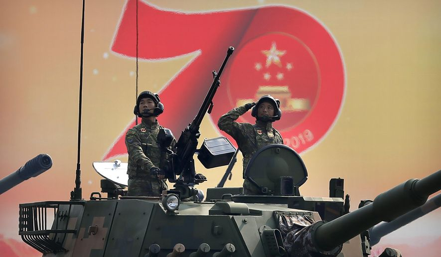 In this Oct. 1, 2019, file photo, Chinese tank crew members salute during a parade to commemorate the 70th anniversary of the founding of Communist China in Beijing. (AP Photo/Mark Schiefelbein, File)