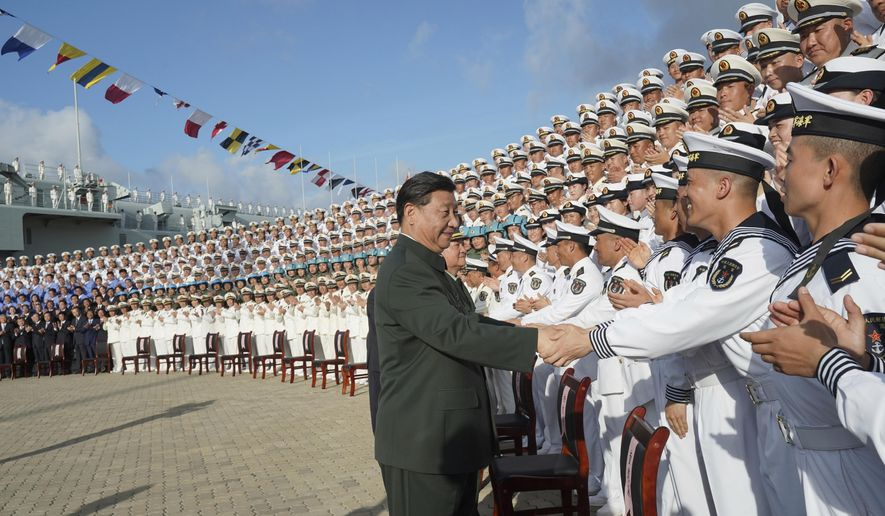 FILE - In this Dec. 17, 2019, file photo and provided by China's Xinhua News Agency, Chinese President Xi Jinping, center, meets with representatives of the aircraft carrier unit and the manufacturer at a naval port in Sanya, southern China's Hainan Province. Seventy-five years after Japan's surrender in World War II, and 30 years after its economic bubble popped, the emergence of a 21st century Asian power is shaking up the status quo. As Japan did, China is butting heads with the established Western powers, which increasingly see its growing economic and military prowess as a threat. (Li Gang/Xinhua News Agency via AP, File)