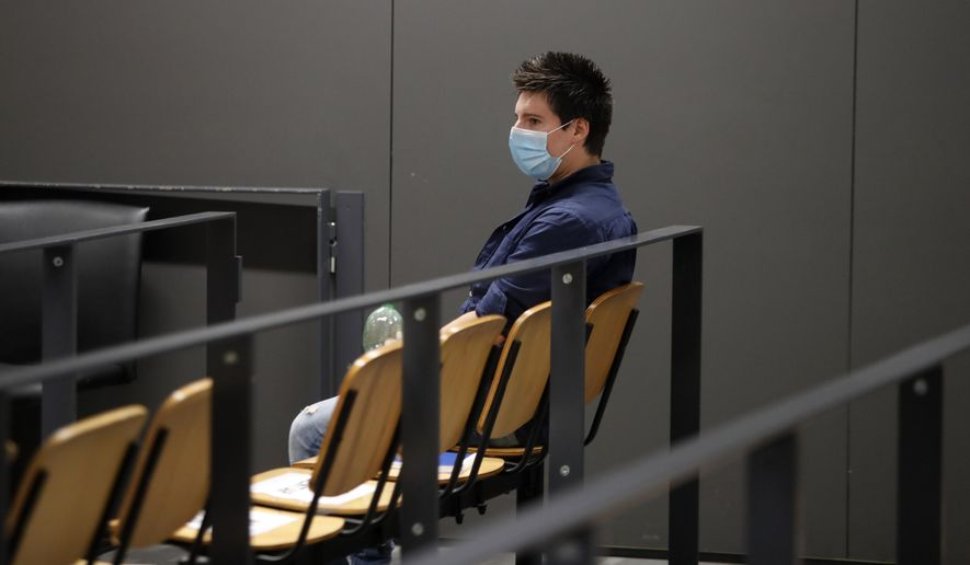 Portuguese hacker Rui Pinto sits in the courtroom at the start of his trial in Lisbon, Friday, Sept. 4, 2020. Lisbon court is hearing the case against 31-year-old Pinto, whose expose was published over financial revelations about European soccer players, top clubs, influential agents and continental officials. (AP Photo/Armando Franca)