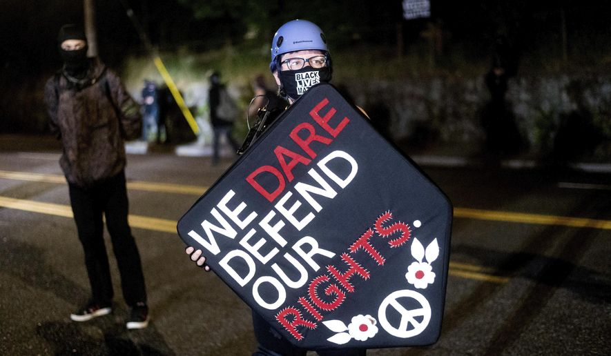Stacy Kendra Williams holds a shield while facing off against police at the Penumbra Kelly Building on Thursday, Sept. 3, 2020, in Portland, Ore. This weekend Portland will mark 100 consecutive days of protests over the May 25 police killing of George Floyd.  (AP Photo/Noah Berger)