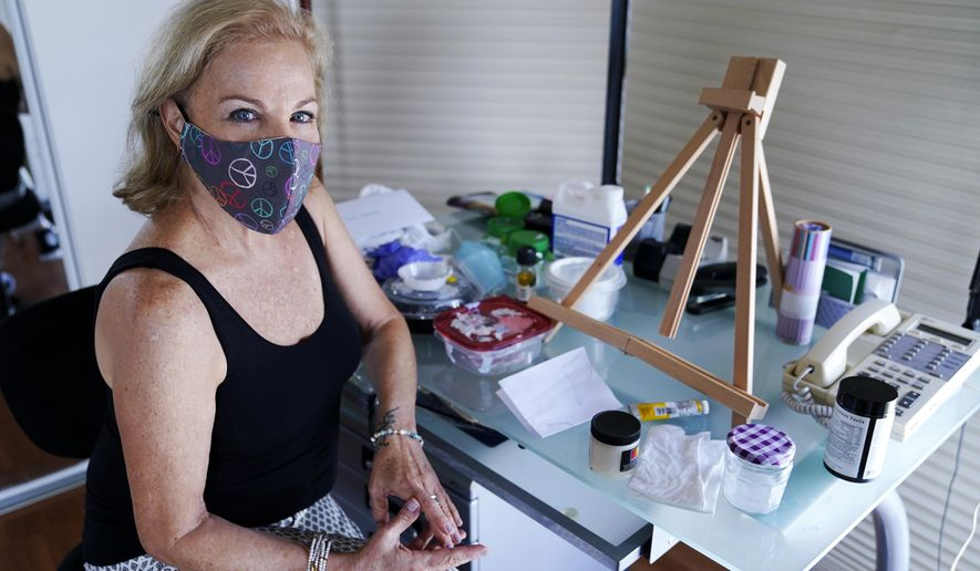 Artist Irene Pressner poses for a photograph on Aug. 21, 2020, in Aventura, Fla. The Venezuelan artist, a COVID-19 survivor who lost her husband to the virus, is creating new works inspired by her experience. (AP Photo/Lynne Sladky)