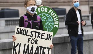 """Swedish climate activist Greta Thunberg holds a poster reading """"School strike for Climate"""" as she protests in front of the Swedish Parliament Riksdagen, in Stockholm, Friday Sept. 4, 2020.  The 17-year-old Swedish climate activist Greta Thunberg said Monday she is heading back to school after a year off, but has resumed her weekly climate protests outside Sweden's parliament. (Fredrik Sandberg / TT via AP)"""