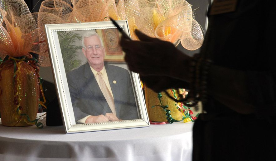 A person entering a memorial service for Mayor Billy Joe Driver in Clanton, Ala., walks past a photo of the longtime public official on Friday, Aug. 28, 2020. Driver's death of COVID-19 shocked the central Alabama community, where residents say many people thought the illness caused by the new coronavirus was a big-city problem until he succumbed. (AP Photo/Jay Reeves)