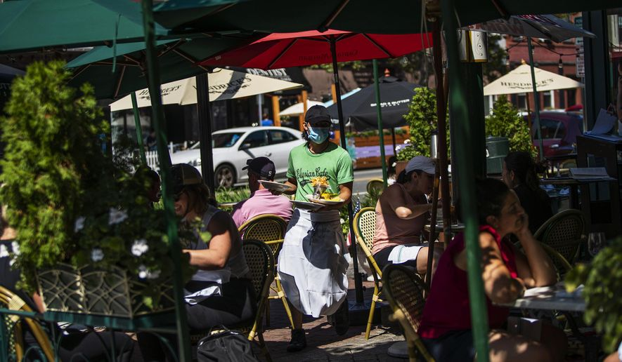 A waiter in a face mask delivers food to the tables outside of a local restaurant during lunch on Friday, Sept. 4, 2020, in Hoboken, N.J. (AP Photo/Eduardo Munoz Alvarez)