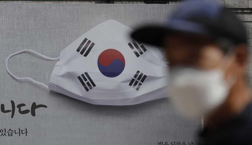 A man wearing a face mask walks near a banner displaying as a part of campaign to overcome the coronavirus in Seoul, South Korea, Friday, Sept. 4, 2020. (AP Photo/Lee Jin-man)