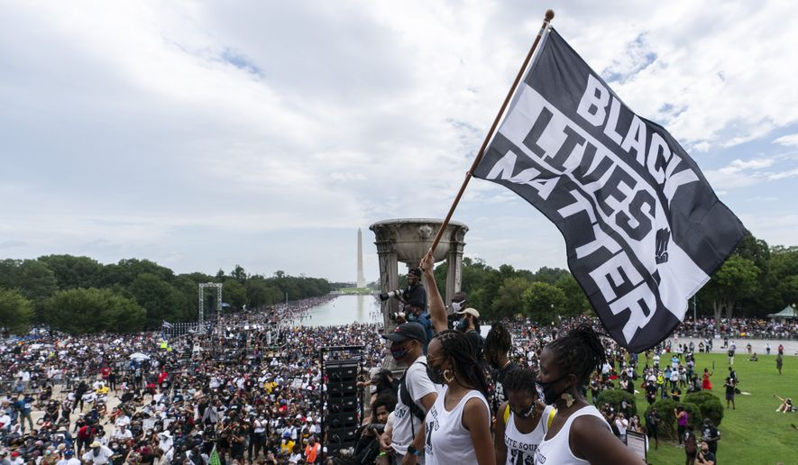 "In this file photo, a woman holds a ""Black Lives Matter,"" flag during the March on Washington, Friday Aug. 28, 2020, at the Lincoln Memorial in Washington.  (AP Photo/Alex Brandon)  **FILE**"