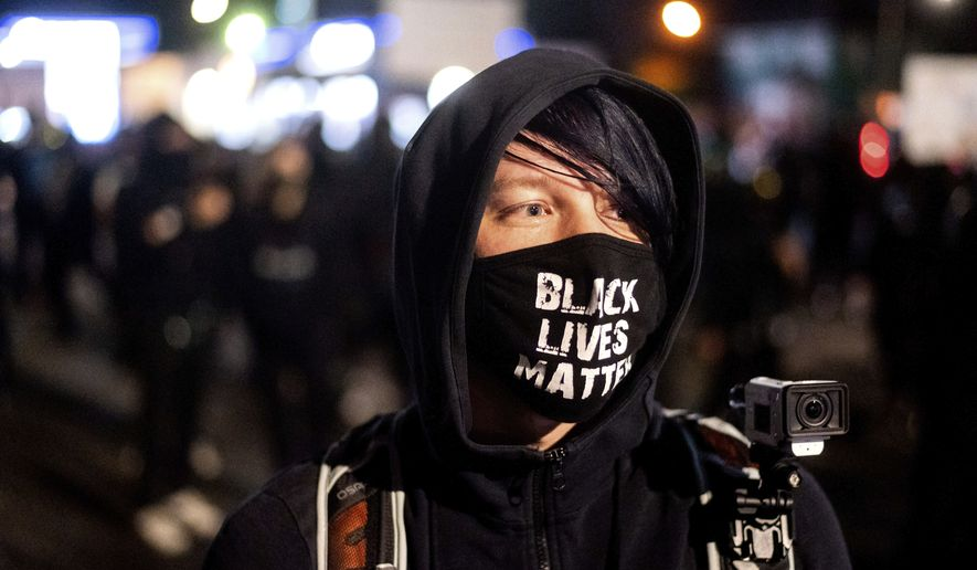 A Black Lives Matter protester, who declined to give his name, rallies outside the Portland Police Association building on Friday, Sept. 4, 2020, in Portland, Ore. This weekend Portland will mark 100 consecutive days of protests over the May 25 police killing of George Floyd.  (AP Photo/Noah Berger)