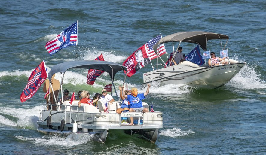 A Trump masked boat rider waves to those on the Hwy 421 bridge during the South Holston Trump Boat Parade on Saturday, Sept. 5, 2020 in Bristol, Tenn. (Earl Neikirk/Bristol Herald Courier via AP)