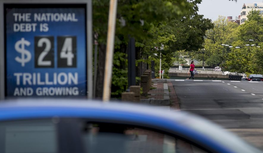 In this April 29, 2020 file photo, a sign displaying the size of the national debt is displayed along an empty K Street in Washington. The Congressional Budget Office has warned that the government this year will run the largest budget deficit, as a share of the economy, since 1945, the year World War II ended. Next year, the federal debt — made up of the year-after-year gush of annual deficits — is forecast to exceed the size of the entire American economy for the first time since 1946. (AP Photo/Andrew Harnik, File)