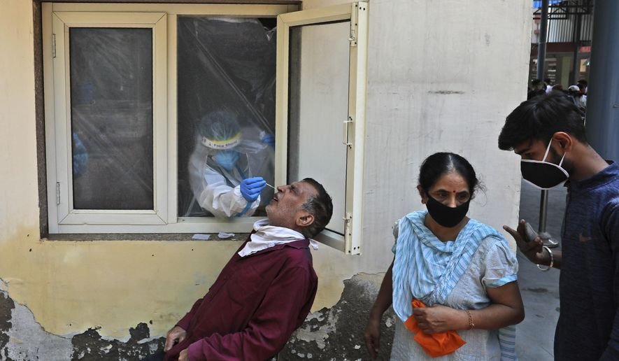 A health worker takes a nasal swab sample to test for COVID-19 in New Delhi, India, Saturday, Sept. 5, 2020. India's coronavirus cases have crossed 4 million, leading the world in new infections and deepening misery in the country's vast hinterlands where surges have crippled the underfunded health care system. Initially, the virus ravaged India's sprawling and densely populated cities. It has since stretched to almost every state, spreading through villages. (AP Photo/Manish Swarup)