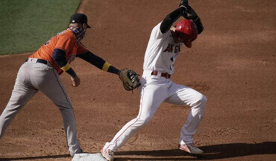 Los Angeles Angels' Shohei Ohtani, right, of Japan, avoids a tag from Houston Astros first baseman Yuli Gurriel during the first inning of the first baseball game of a doubleheader, Saturday, Sept. 5, 2020, in Anaheim, Calif. (AP Photo/Jae C. Hong)
