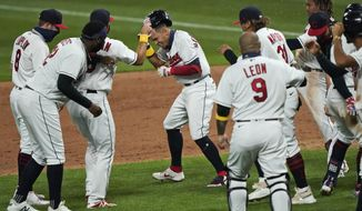 Cleveland Indians' Cesar Hernandez, center, is mobbed by teammates after hitting an RBI-single in the ninth inning in a baseball game against the Milwaukee Brewers, Saturday, Sept. 5, 2020, in Cleveland. (AP Photo/Tony Dejak)