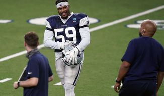 Dallas Cowboys defensive end Justin March (59) smiles as he prepares for drill during an NFL football training camp practice in Frisco, Texas, Monday, Aug. 31, 2020. (AP Photo/LM Otero)