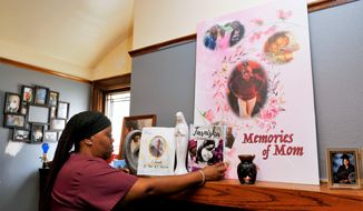 This Aug. 2020 photo shows Wyconda Clayton looking over a memorial honoring the sudden passing of three family members just months apart this year in Milwaukee. Her mother Eula Clayton died April 14, God-sister Tarnisha Young died May 20, and her oldest sister Sarah Clayton died June 23.  Clyton is fighting an eviction notice.   (Pat A. Robinson via AP)