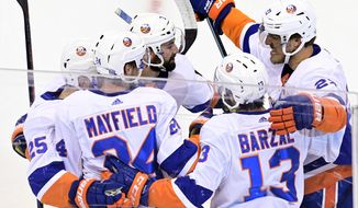 New York Islanders defenseman Scott Mayfield (24) celebrates his goal against the Philadelphia Flyers with teammates during first-period NHL Stanley Cup Eastern Conference playoff hockey game action in Toronto, Saturday, Sept. 5, 2020. (Frank Gunn/The Canadian Press via AP)