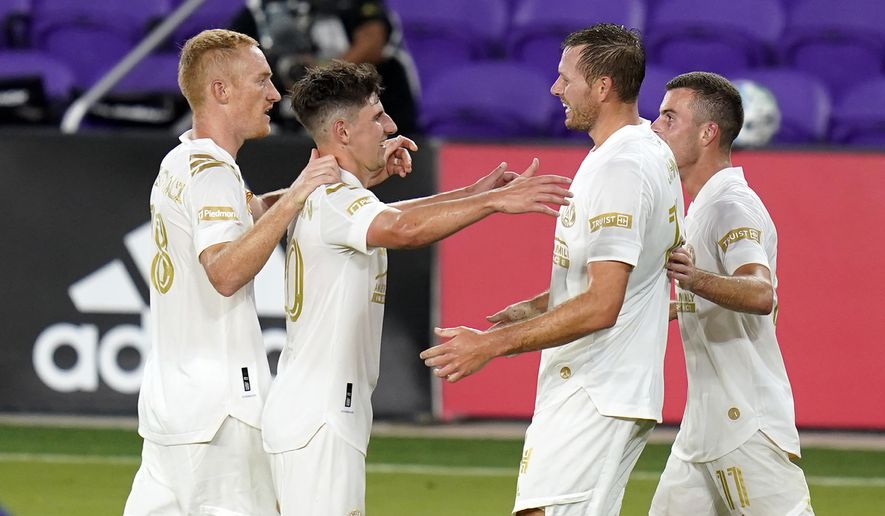 Atlanta United forward Adam Jahn, second from right, celebrates after scoring a goal against Orlando City with teammates, from left to right, Jeff Larentowicz, Emerson Hyndman and Brooks Lennon (11) during the second half of an MLS soccer match, Saturday, Sept. 5, 2020, in Orlando, Fla. (AP Photo/John Raoux)