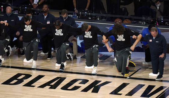 FILE - In this Aug. 29, 2020, file photo, members of the Milwaukee Bucks join arms as they kneel during the national anthem before an NBA basketball first round playoff game against the Orlando Magic Saturday, in Lake Buena Vista, Fla. Ahead of Labor Day, major U.S. labor unions say they are considering work stoppages in support of the Black Lives Matter movement. The unions say they're following the lead of professional athletes who last week staged strikes to protest the shooting of Jacob Blake in Kenosha, Wis. (AP Photo/Ashley Landis, File)