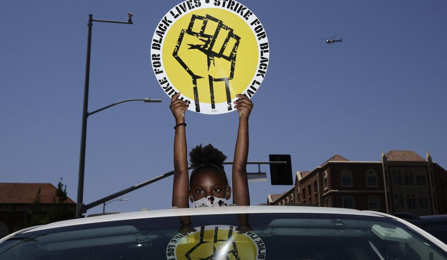 In this July 20, 2020, file photo, Audrey Reed, 8, holds up a sing through the sunroof of a car during a rally in Los Angeles. Ahead of Labor Day, major U.S. labor unions say they are considering work stoppages in support of the Black Lives Matter movement. (AP Photo/Jae C. Hong, File)  **FILE**