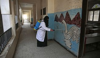 A worker disinfects a school as a preventive measure against the spread of the new coronavirus before students taking a final-term school exam at a public school in Sanaa, Yemen, Saturday, Aug. 29, 2020. (AP Photo/Hani Mohammed)