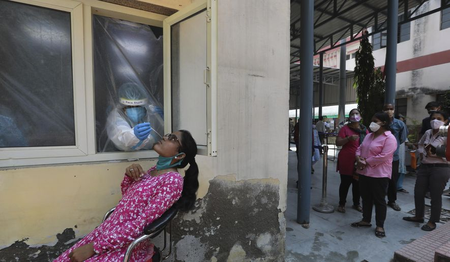 A health worker takes a nasal swab sample to test for COVID-19, as others await their turn in New Delhi, India, Saturday, Sept. 5, 2020. India's coronavirus cases have crossed 4 million, leading the world in new infections and deepening misery in the country's vast hinterlands where surges have crippled the underfunded health care system. Initially, the virus ravaged India's sprawling and densely populated cities. It has since stretched to almost every state, spreading through villages. (AP Photo/Manish Swarup)