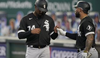 Chicago White Sox's Eloy Jimenez (74) is congratulated by Tim Anderson after scoring a run during the first inning of the team's baseball game against the Kansas City Royals at Kauffman Stadium in Kansas City, Mo., Friday, Sept. 4, 2020. (AP Photo/Orlin Wagner)