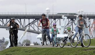 A Seattle Police Officer on a bicycle watches from a hill as people ride by at Gas Works Park in Seattle, Sunday, April 26, 2020. The park and others in Seattle were open Sunday, but officials sought to prevent the spread of the coronavirus by urging people to keep moving and not to gather in large groups. (AP Photo/Ted S. Warren)
