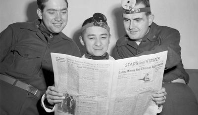 Former Olympic diver Sammy Lee, with co-workers at the hospital in Seoul, Korea, read the news of his award in the Stars and Stripes, Dec. 1953. From left: Cpl. Homer R. Banham of Paris, Mo.; Lee; and Capt. Jules A Howell of Winston-Salem, N.C. (AP Photo/George Sweers) ** FILE **