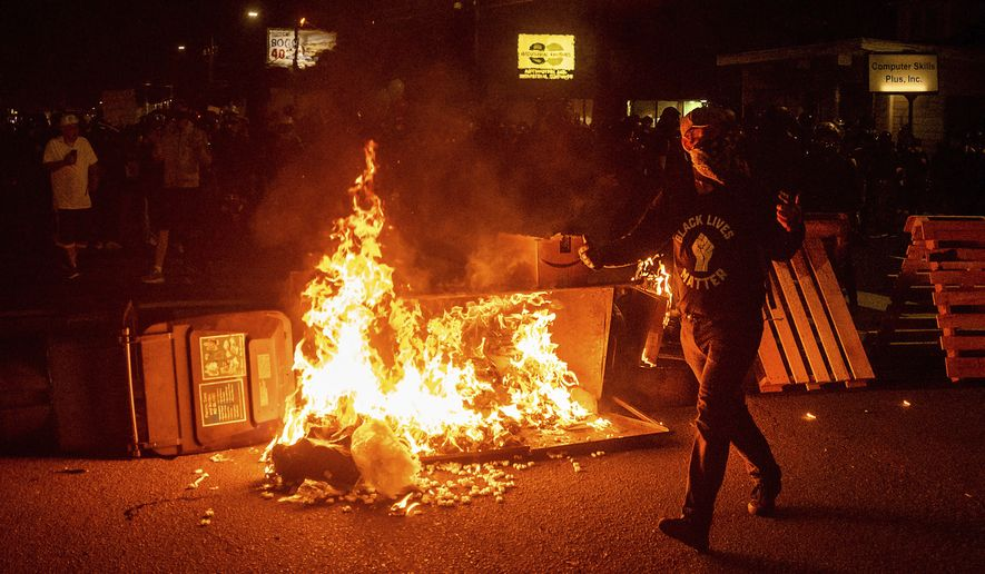 An activist passes a dumpster fire on Saturday, Sept. 5, 2020, during a demonstration in Portland, Ore. Hundreds of people gathered for rallies and marches against police violence and racial injustice Saturday night in Portland, Oregon, as often violent nightly demonstrations that have happened for 100 days since George Floyd was killed showed no signs of ceasing. (AP Photo/Noah Berger)
