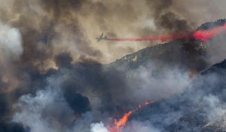 An air tanker drops retardant at a wildfire burns at a hillside in Yucaipa, Calif., Saturday, Sept. 5, 2020. Three fast-spreading wildfires sent people fleeing and trapped campers in one campground as a brutal heat wave pushed temperatures above 100 degrees in many parts of California. (AP Photo/Ringo H.W. Chiu)