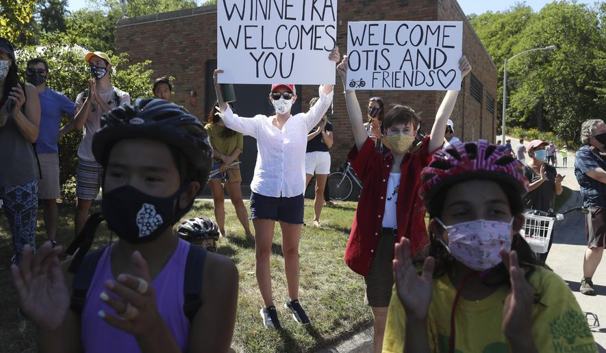 Supporters of Otis Campbell raise signs at a rally after a bicycle ride to Tower Road Beach Saturday, Sept. 5, 2020, in Winnetka, Ill. About 75 bicyclists rode with Campbell from Tower Road Boat Launch in Northfield to Tower Road Beach as a gesture of solidarity, after an Aug. 17 incident when Campbell was harassed and threatened by area resident Irene Donoshaytis for being at the beach pier with friends following a 15-mile bicycle ride. (John J. Kim/Chicago Tribune via AP)