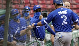 Toronto Blue Jays' Joe Panik (2) is welcomed to the dugout after scoring on a double by Cavan Biggio, not shown, in the fifth inning of a baseball game against the Boston Red Sox, Sunday, Sept. 6, 2020, in Boston. (AP Photo/Steven Senne)