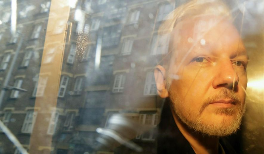 In this Wednesday, May 1, 2019 file photo, buildings are reflected in the window as WikiLeaks founder Julian Assange is taken from court, where he appeared on charges of jumping British bail seven years ago, in London. (AP Photo/Matt Dunham, File)
