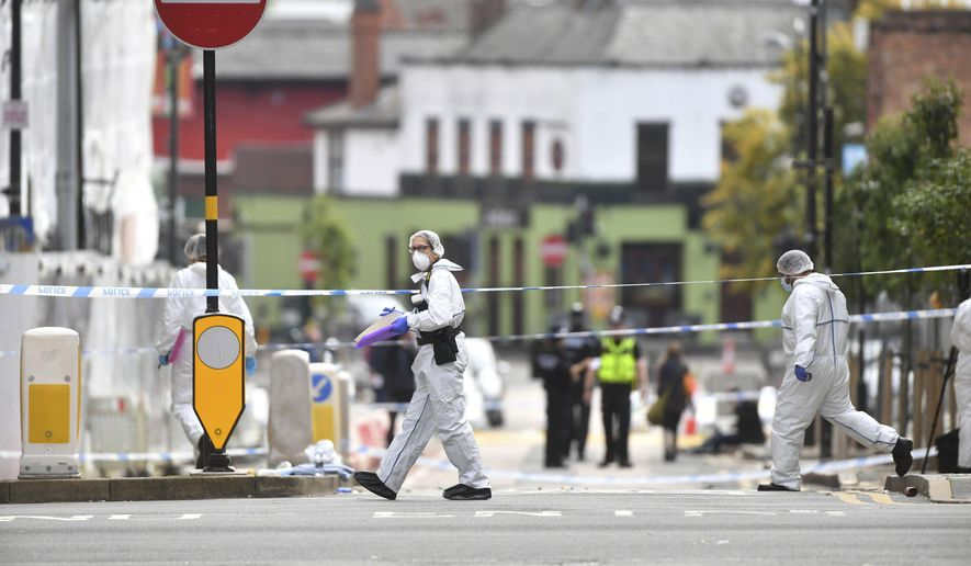 Police forensic officers investigate after stabbings in Birmingham, northern England, Sunday Sept. 6, 2020.  Police were called to the scene after a number of people were reported to be stabbed in the city centre, in the early hours of Sunday.  (Jacob King/PA via AP)