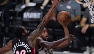 Milwaukee Bucks' Khris Middleton shoots past Miami Heat's Andre Iguodala during the second half of an NBA conference semifinal playoff basketball game Sunday, Sept. 6, 2020, in Lake Buena Vista, Fla. (AP Photo/Mark J. Terrill)