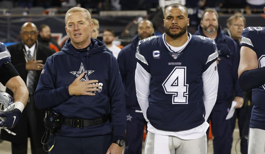 """FILE - In this Dec. 5, 2019, file photo, Dallas Cowboys coach Jason Garrett and quarterback Dak Prescott (4) listen to the national anthem before the team's NFL football game against the Chicago Bears in Chicago.  Prescott wants his teammates to decide for themselves whether to protest during the national anthem. Defensive lineman Tyrone Crawford says they have the """"green light"""" to do so. Owner Jerry Jones hasn't said in so many words, but it appears his hard-line stance over his players standing during the anthem has eased amid a national reckoning over racial justice. (AP Photo/Charles Rex Arbogast, File)"""