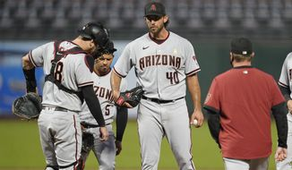 Arizona Diamondbacks starting pitcher Madison Bumgarner (40) stands on the mound and waits for a conference with pitching coach Matt Herges as catcher Carson Kelly and third baseman Eduardo Escobar (5) stand nearby during the fourth inning of the team's baseball game against the San Francisco Giants on Saturday, Sept. 5, 2020, in San Francisco. (AP Photo/Eric Risberg)