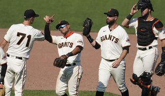 San Francisco Giants' Tyler Rogers, from left, celebrates with Donovan Solano, Brandon Belt and Joey Bart after the Giants defeated the Arizona Diamondbacks in a baseball game in San Francisco, Sunday, Sept. 6, 2020. (AP Photo/Jeff Chiu)