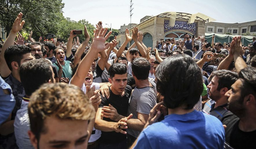 In this June 25, 2018 file photo, a group of protesters chant slogans at the main gate of the Old Grand Bazaar, in Tehran, Iran. On Saturday, Sept. 5, 2020, Iran broadcast the televised confession of a wrestler facing the death penalty after a tweet from President Donald Trump criticizing the case, a segment that resembled hundreds of other suspected coerced confessions aired over the last decade in the Islamic Republic. (Iranian Labor News Agency via AP, File)  **FILE**