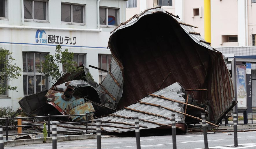 The roof of a car factory is left on the sidewalk after a typhoon hit Fukuoka, southwestern Japan, Monday, Sept. 7, 2020. The second powerful typhoon to slam Japan in a week left people injured, damaged buildings, caused blackouts at nearly half a million homes and paralyzed traffic in southern Japanese islands before headed to South Korea. (Kyodo News via AP)