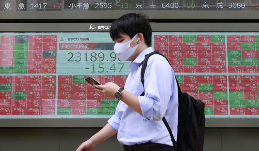 A man walks by an electronic stock board of a securities firm in Tokyo, Monday, Sept. 7, 2020. Asian stock markets were mixed Monday after Wall Street turned in its biggest weekly decline in more than two months.(AP Photo/Koji Sasahara)