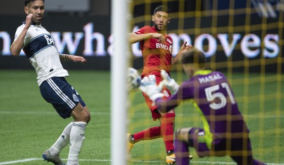 Toronto FC's Jonathan Osorio, back right, scores against Vancouver Whitecaps goalkeeper Thomas Hasal (51) as Erik Godoy, left, watches during the first half of an MLS soccer match Saturday, Sept. 5, 2020, in Vancouver, British Columbia. (Darryl Dyck/The Canadian Press via AP)