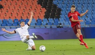 Switzerland's Silvan Widmer, right, scores past Germany's Robin Gosens, left,  during their UEFA Nations League soccer match at the St. Jakob-Park stadium in Basel, Switzerland, on Sunday, Sept. 6, 2020. (Georgios Kefalas/Keystone via AP)