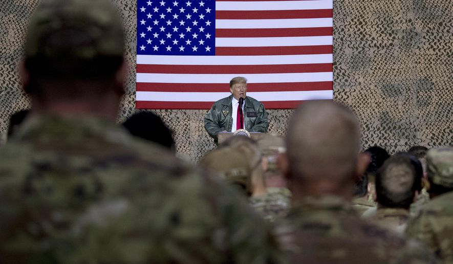 FILE - In this Dec. 26, 2018, file photo, President Donald Trump speaks to members of the military at a hangar rally at Al Asad Air Base, Iraq. Among veterans and military families across the United States, there are sharply mixed feelings about the new reports that Trump made multiple disparaging comments about the U.S. military. (AP Photo/Andrew Harnik, File)